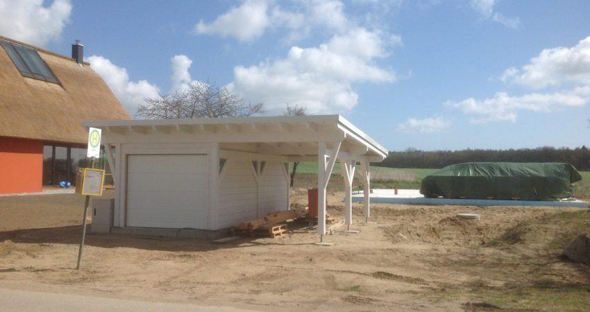 Bushaltestelle ohne Befestigung oder Wartehäuschen. Im Hintergrund eine Garage mit Überstand aus Holz.
